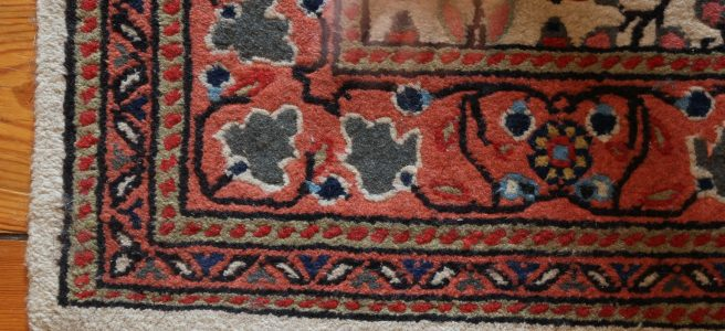 a photograph of the corner of a patterned floor rug. a woman's blurred hand is at the top of the image