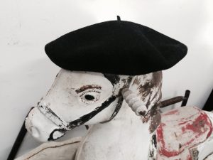 The head of a battered wooden rocking horse with a black felt cap on it's head