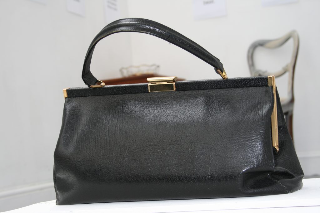 a black vintage handbag with gold clasp and hinges