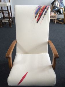 an armchair with wooden arms and white upholstery with bright slashes of colour on the back and seat