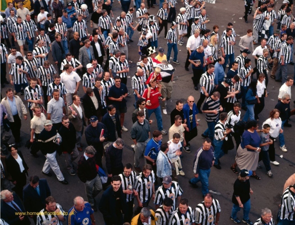 a crowd of football supporters. some are wearing black and white striped shirts