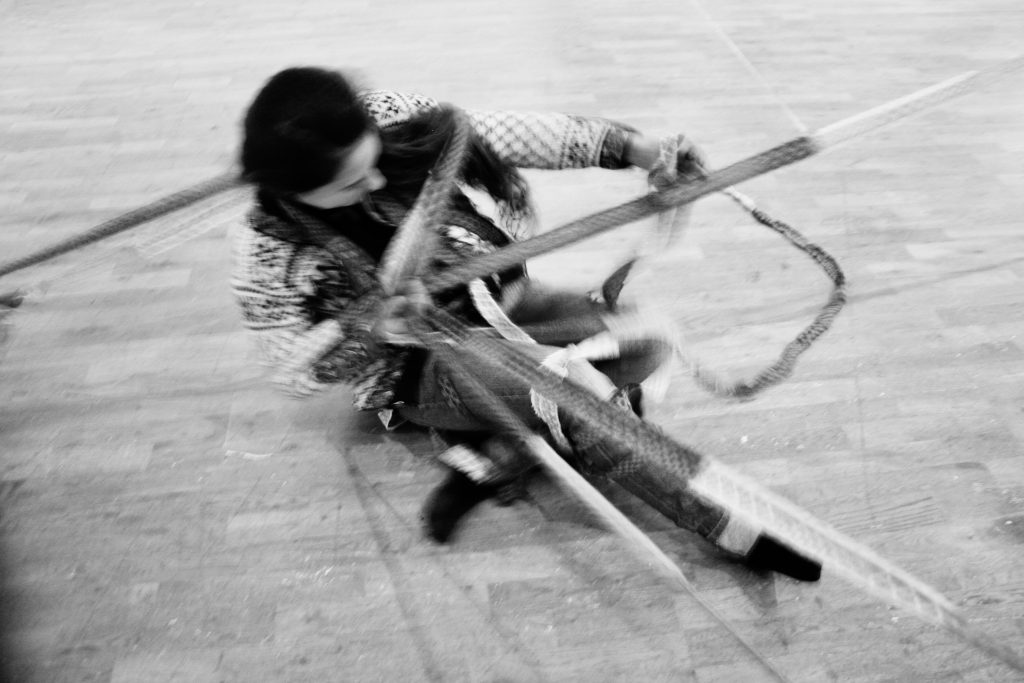 a black and white photgraph of a woman sitting on the floor pulling on a tangle of ropes some of which are wrapped around her body