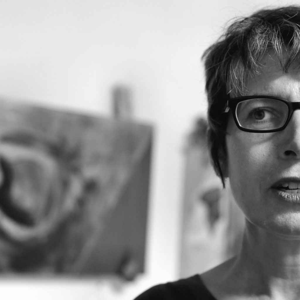 Black and white photo of half of a woman's face. she is talking, there is an out of focus painting behind her