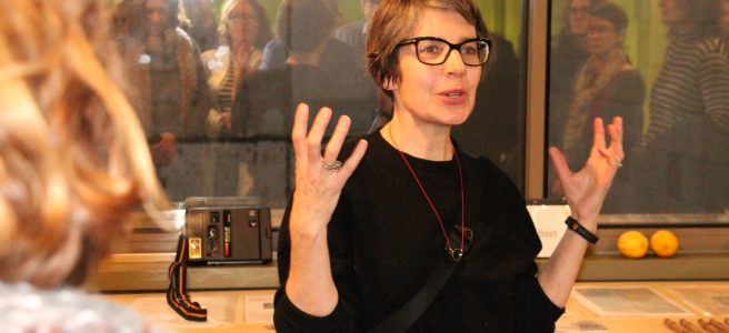 a woman with short hair and glasses talking and gesturing in front of a small group of people