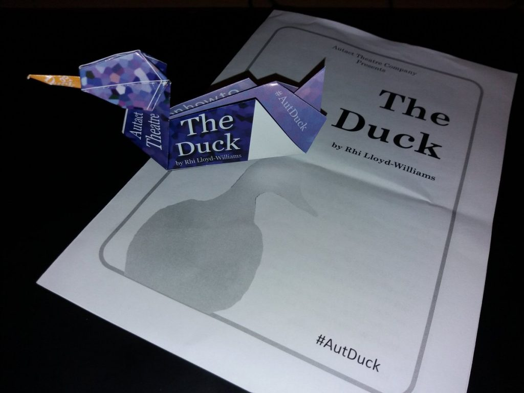 an origami duck sitting on top of a theatre playbill