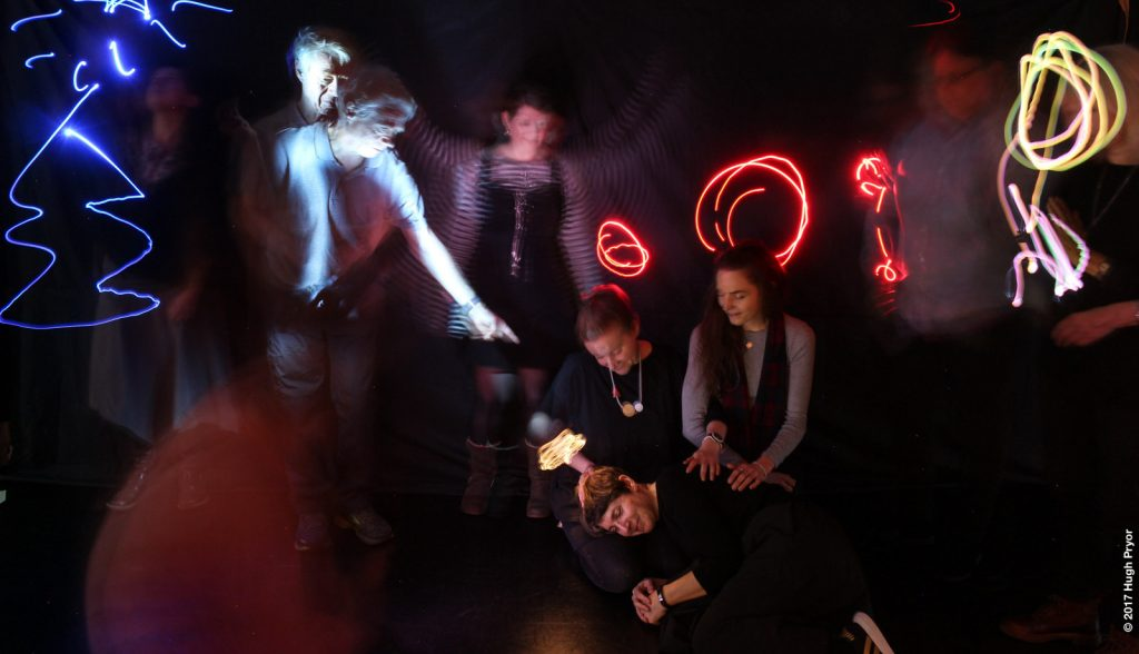 Smiling people in a darkened space, some sitting, some standing, with bright graphical designs made with light
