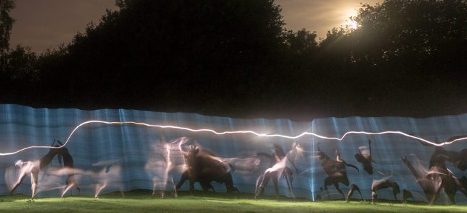Photograph of figures in a landscape at night with trails of light.