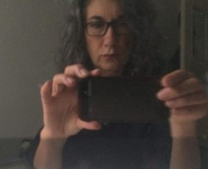 A woman with long hair and glasses taking a photograph of herself in a mirror