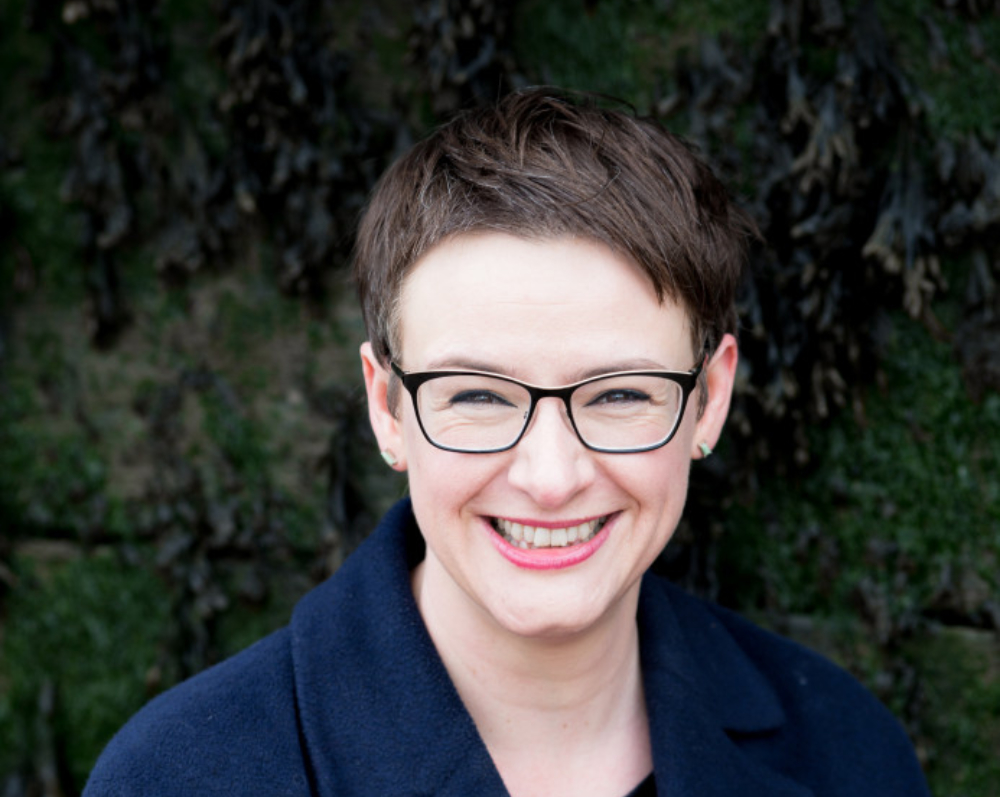 woman with short dark hair and glasses smiling to camera.