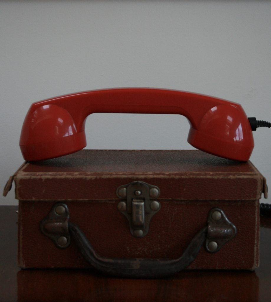 A red, retro telephone reciever lying on top of a vintage suitcase.