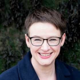 portrait photo of a smiling woman with short hair and glasses