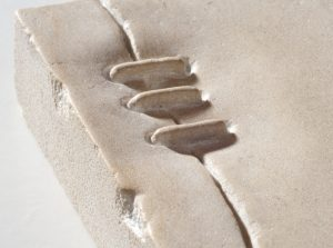 detail image of a stone carving representing leather lacing on a handbag
