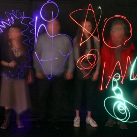 a blurred photo of 4 people overlaid with brightly coloured graphical shapes