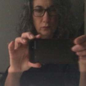 woman with curly hair and glasses taking a her photo in a mirror