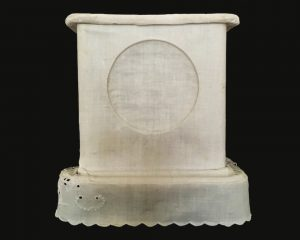 A photograph of a clock case covered with white linen