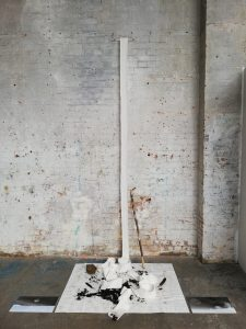 white knitted object hanging from wall to an open map on the floor. With soil, a birds nest, a walking stick and two landscape photographs