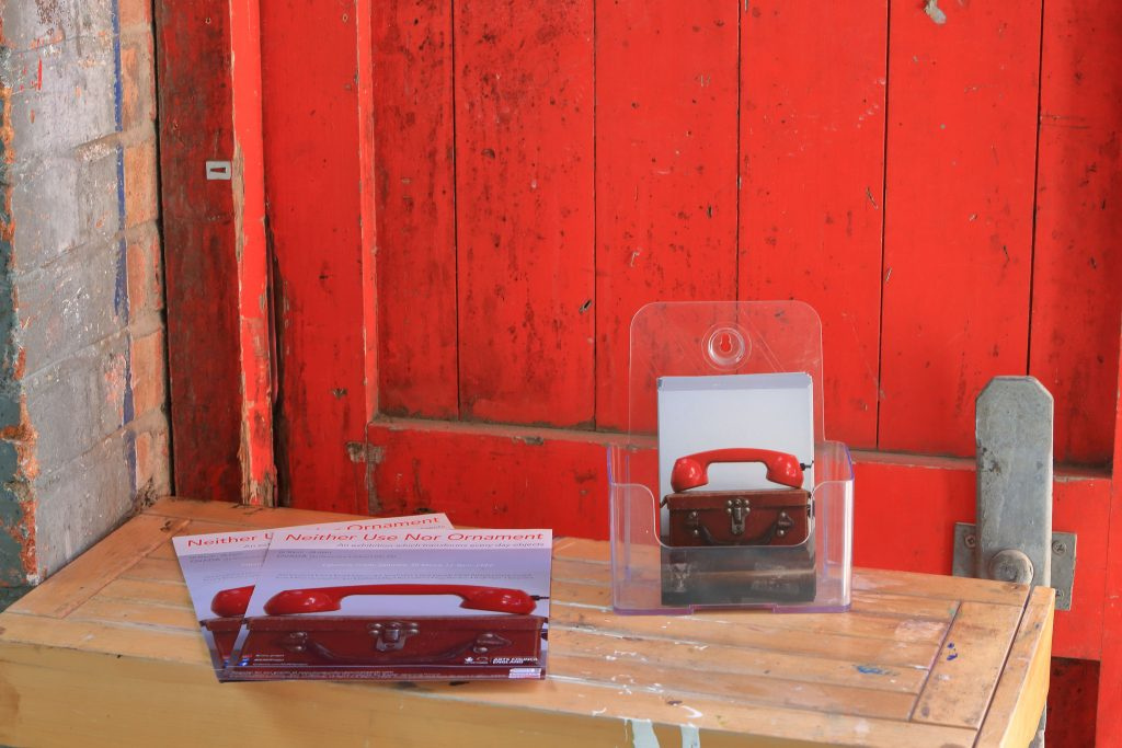 a pile of leaflets on a table in front of a red, wooden door