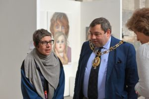 A woman wearing a grey shawl talks to a man wearing a mayor's chain in front of a large portrait of a woman's face