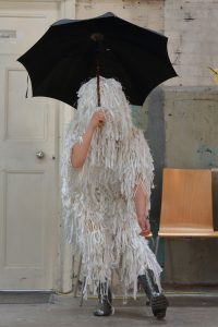 A person covered from head to knees in tattered white yarns carrying a black umbrella and wearing silver wellington boots