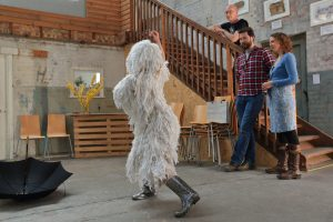 a person covered in a white tasseled costume and silver wellingtons dances in front of a small audience of people.