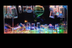 A selection of clear glass bottles suspended in a water tank and lit with multi coloured lights